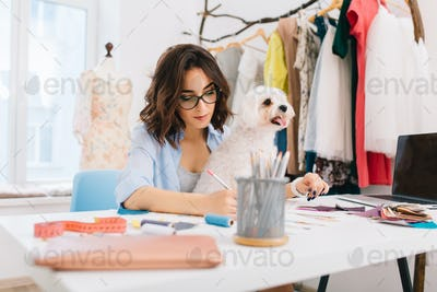 A brunette girl in a blue shirt is sitting at the table in the workshop . She is deawing some