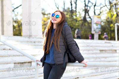 Stylish city portrait of ginger petty woman, walking alone at Europe
