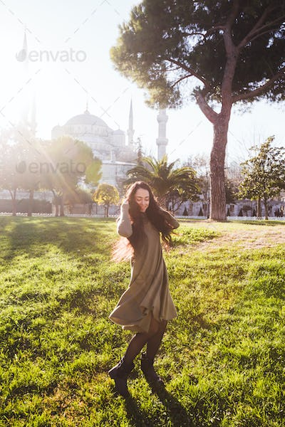 Happy woman in a beige dress whirls in a dance near the Blue Mosque at sunny weather