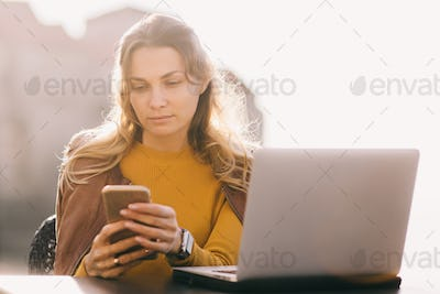 serious young business woman work on laptop and smartphone outdoors
