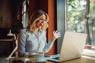 Close shot of smiled blonde woman having online call on laptop while sitting in cafe