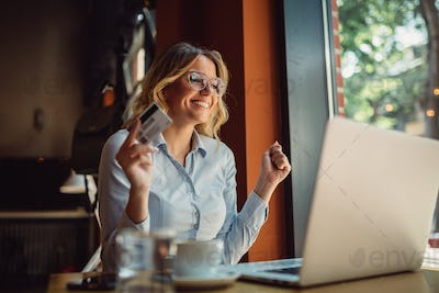 Portrait of blonde business woman shopping online while sitting in cafeteria