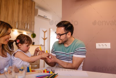 Cute little girl and her father are playing together with toys