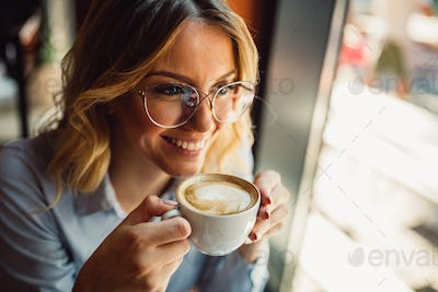 Portrait of beautiful young business woman drinking coffee in cafe during coffee break