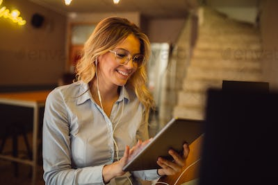 Portrait of beautiful blonde woman with earphones having online call on tablet computer