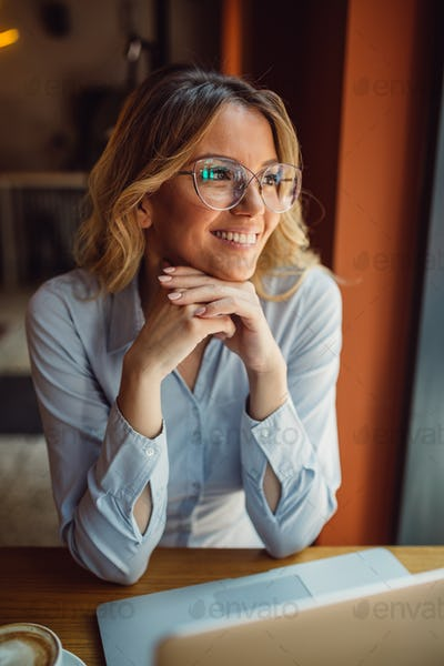 Beautiful young woman with glasses is sitting in cafe and looking through a window in a distance