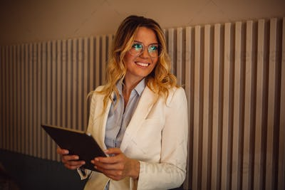 Beautiful blonde woman with glasses wearing blue shirt and white jacket holding tablet computer
