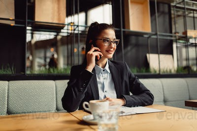 Young woman wearing spectacles talking on mobile.