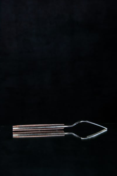 Vertical view of elegant shiny metal fork put upside down on black background with free space