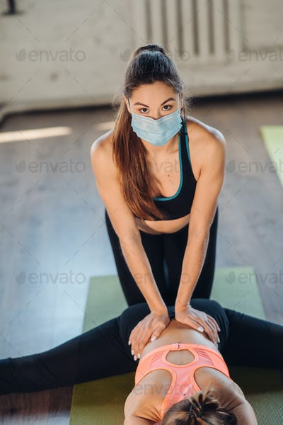 Active sportive woman stretching, young woman helping her