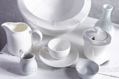 Empty crockery or ceramic dishes set. White kitchen dishware and tableware at wooden old chair