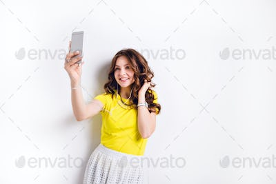 Cute brunette girl listening to music on earphones on smartphone is having fun and takes a selfie