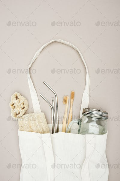 bamboo toothbrushes, organic loofah, jar and stainless steel straws in white cotton bag on grey