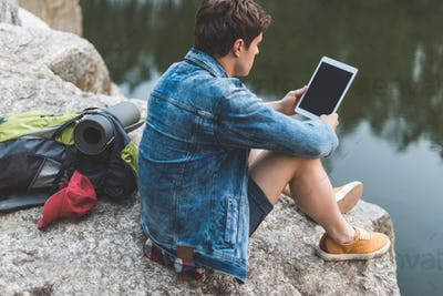 young man with backpack using tablet on nature while sitting on rocky river shore