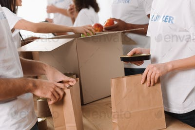 cropped shot of group of volunteers packing food for charity