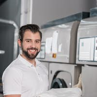 dry cleaning worker holding stack of clean clothes