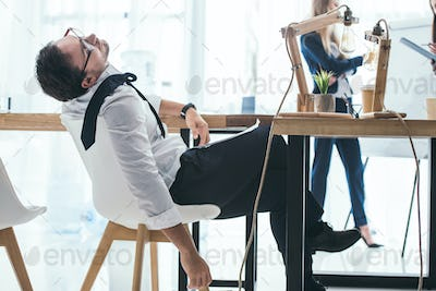 overworked young businessman sleeping on chair at office workplace