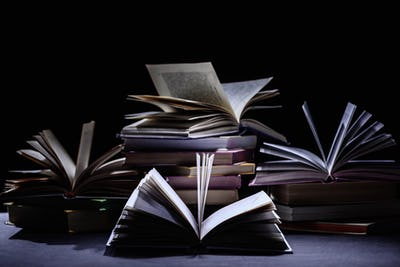 stack of books on dark surface on black