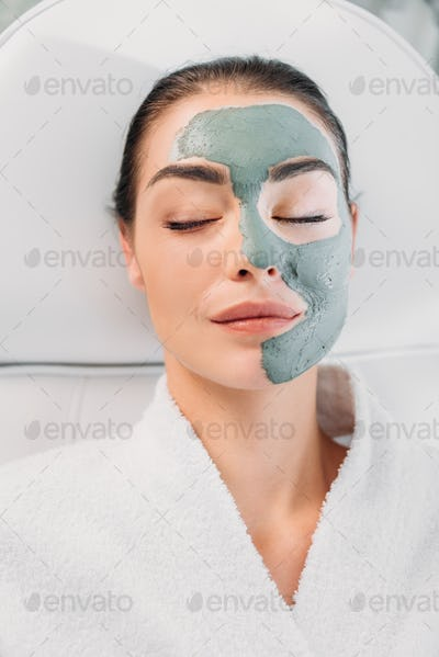 overhead view of beautiful woman with eyes closed and clay mask on face in white bathrobe relaxing