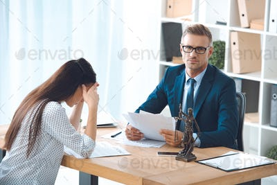 lawyer holding papers and looking at camera while sad female client sitting in office
