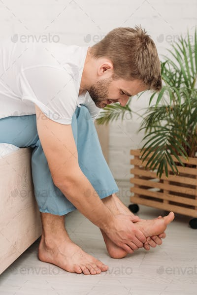 young man touching foot while sitting on bed and suffering from pain