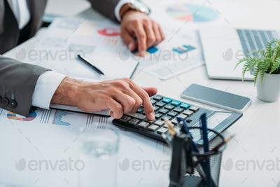 selective focus of young adult man using calculator among documents