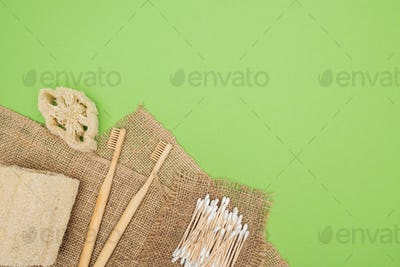 bamboo toothbrushes, organic loofah, cotton swabs and brown sackcloth on light green background