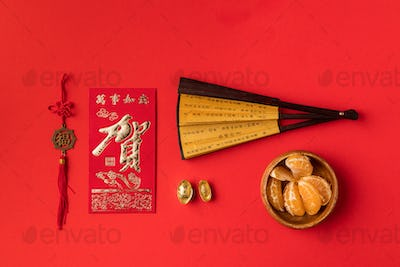 top view of chinese greeting card with calligraphy, oriental fan, decorations and mandarins isolated