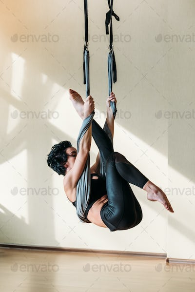 young attractive woman practicing aerial yoga