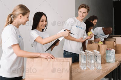 multiethnic young group of volunteers packing food for charity