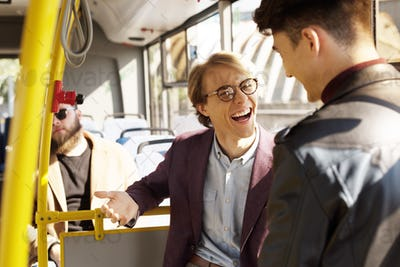 selective focus of cheerful friends having conversation in public transport