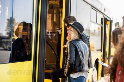 smiling young couple holding hands and entering city bus
