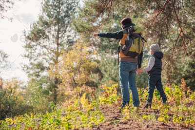 back view of father and son pointing with finger while hiking together
