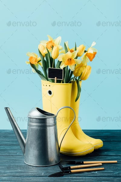 close up view of yellow bouquet of flowers and empty blackboard in rubber boots with watering can