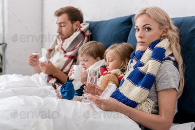 diseased young family sitting in bed together with various treatment methods