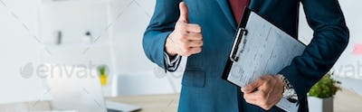 panoramic shot of recruiter standing and holding clipboard with resume letters while showing thumb