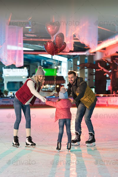 happy family with one child holding heart shaped balloons on skating rink