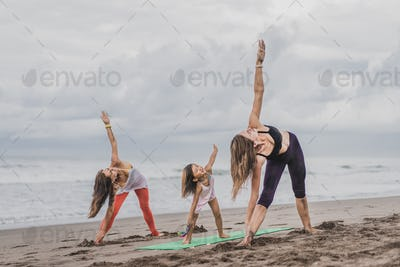 two women and little child practicing yoga on seashore on cloudy day,  Triangle pose (Trikonasana)