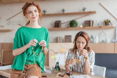 beautiful young women with handmade accessories in workshop