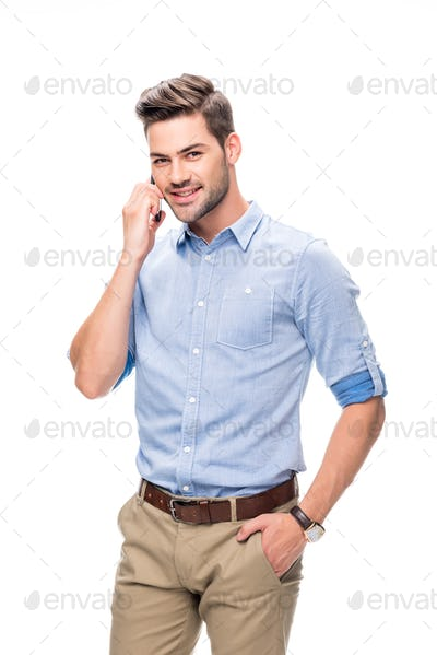 smiling young man talking by phone isolated on white