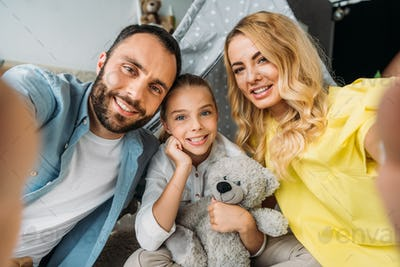 point of view of happy young family taking selfie at home with teepee on background