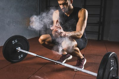 Young sportsman spreading chalk powder in hands for exercising with barbell  in sports hall