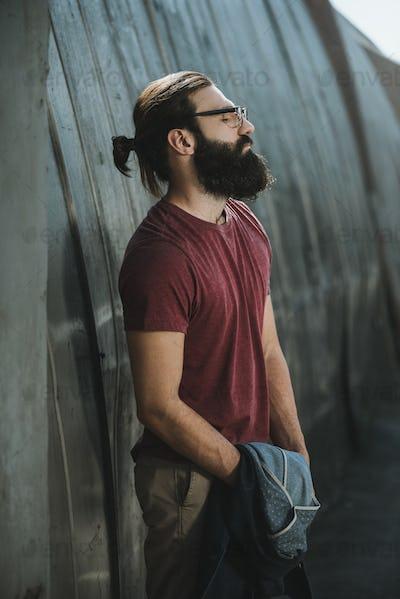 handsome bearded man posing near old hangar