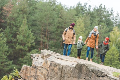 family holding hands standing on rock together in autumn forest