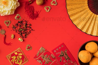 top view of greeting cards with calligraphy, chinese decorations and tangerines isolated on red