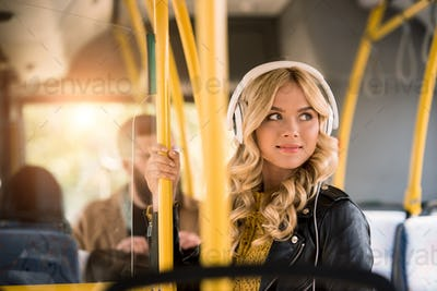 smiling blonde girl in headphones and leather jacket looking away in public transport