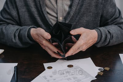 cropped view of male pensioner sitting at table with paperwork and holding empty wallet