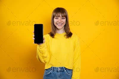 Isolated woman on a yellow background showing showing blank screen mobile phone