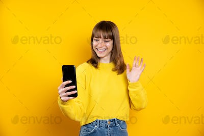 Millennial taking a selfie using smart phone mobile isolated on a yellow background