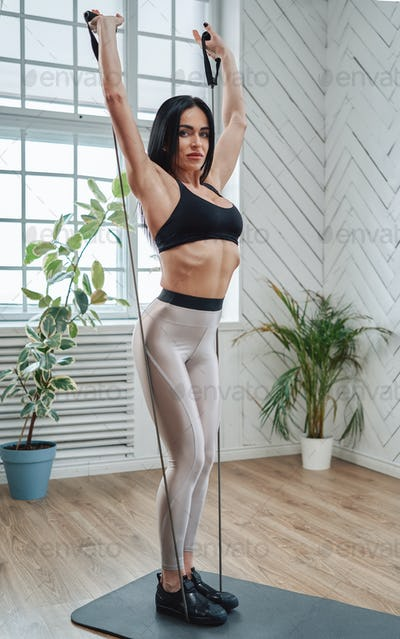 Stretching adult woman dressed in sportswear does workout and relaxes